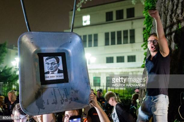 A protester shouts slogans and gestures by a picture of Polish Justice Minister Zbigniew Ziobro stuck on wheelbarrow as a symbol of dismissal during...