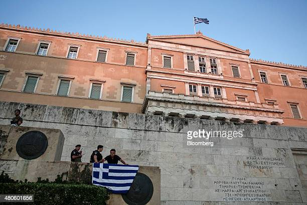 A protester shouts slogans as he holds a Greek national flag in front of policemen during an antiEuropean Union rally outside the parliament in...