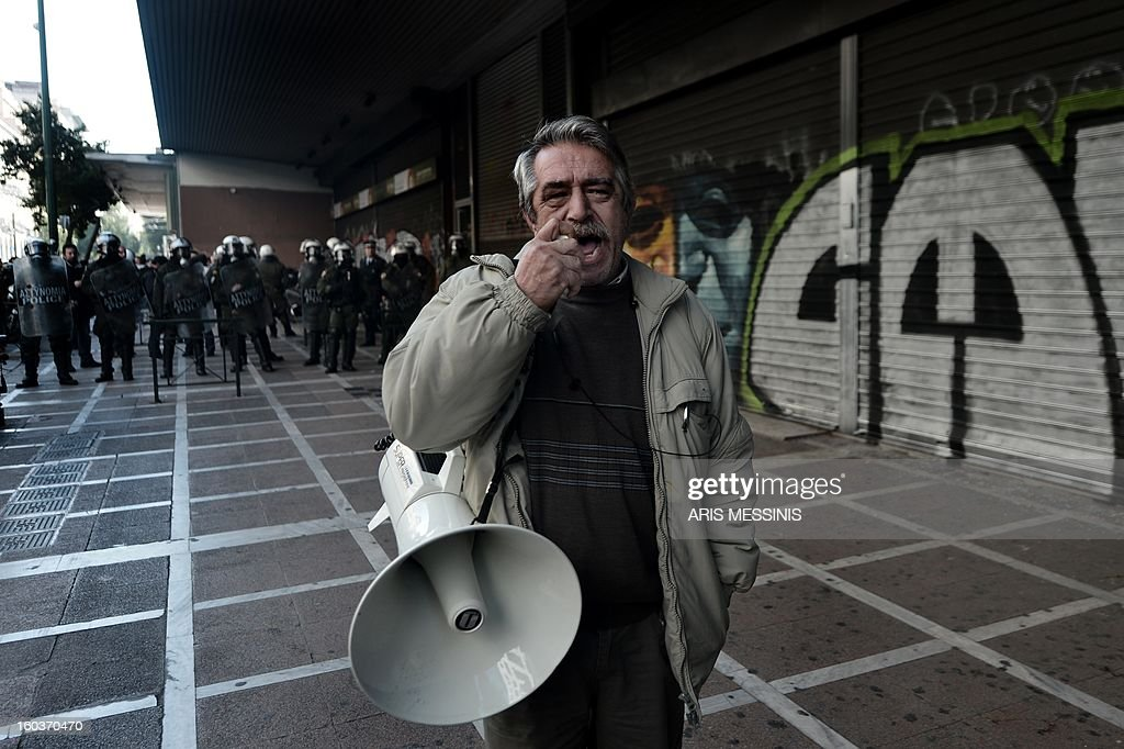 A protester shouts slogans outside the Labour Ministry in Athens on January 30, 2013. Police were called in on Wednesday to dislodge around 30 Communist unionists from the labour ministry in a protest against new pension cut plans. The unionists were arrested and police used tear gas outside the building to disperse a larger group of protesters demanding their release. AFP PHOTO / ARIS MESSINIS