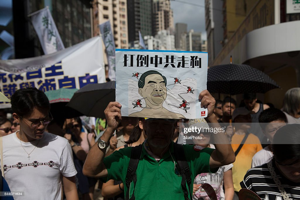 Protester shows a card with a caricature of Hong Kong Chief Executive Leung Chun-ying in Hong Kong, July 1 2016. Pro Democracy protesters march as the city marks the 19th anniversary of the handover from Uk to China.