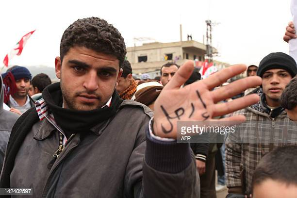 A protester shows the Arabic word written on his palm 'Irhal' during the Crawling Friday demonstration in Wadi Khaled on the LebaneseSyrian border...