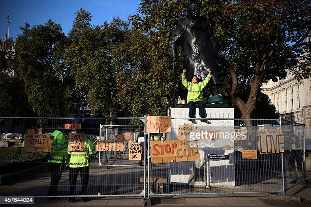 A protester sits on the Winston Churchill statue in Parliament Square on October 22 2014 in London England A small number of antigovernment...