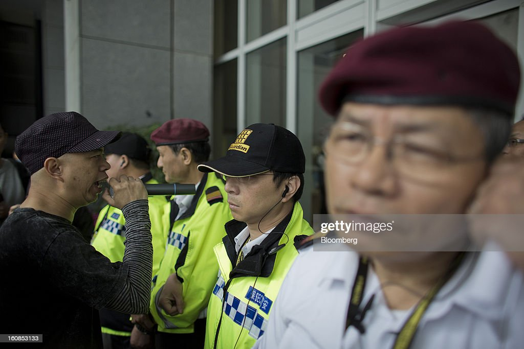 """A protester speaks into a microphone as he stands in front of security personnel at the Central Government Complex during a march organized by labor unions in Hong Kong, China, on Thursday, Feb. 7, 2013. The Financial Services and the Treasury Bureau and the city's Companies Registry put forward a proposal to """"enhance protection of the privacy of personal information,"""" in November as part of a consultation paper on a new companies ordinance. The proposed amendments would make tracing the personal details of company directors in the city more difficult. Photographer: Lam Yik Fei/Bloomberg via Getty Images"""