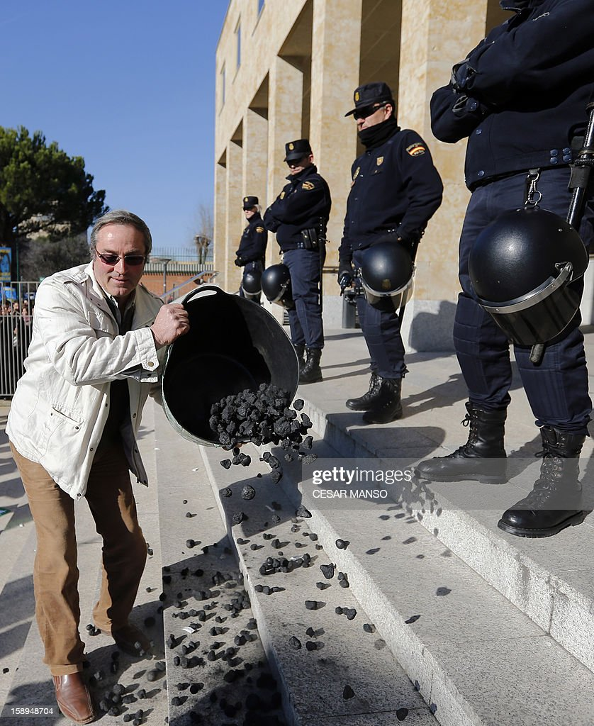 A protester spills coal in front of police officers at Castilla and Leon's Agricultural Ministry during a demonstration against aid cuts in the agricultural sector in Valladolid on January 4, 2013.