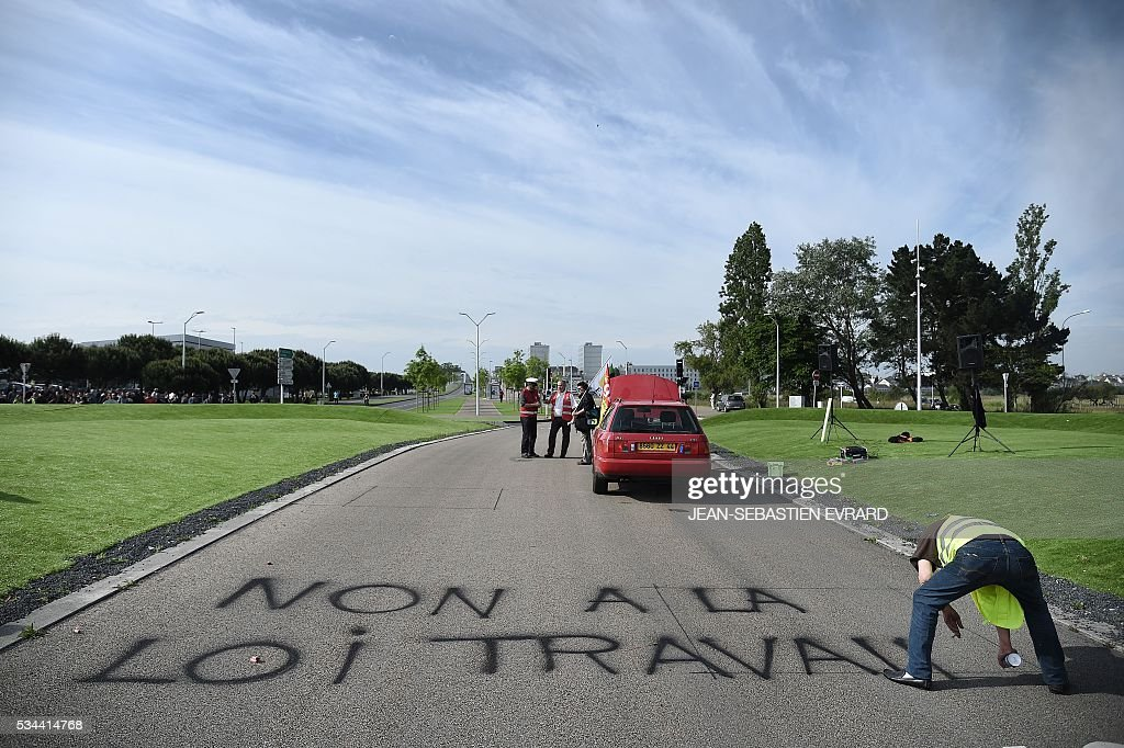 A protester sprays the words,'No to the labour law' as workers and union members gather on May 26, 2016 in Saint-Nazaire, western France, to protest against the government's planned labour law reforms. France's Socialist government has bypassed parliament and rammed through a labour reform bill that has sparked two months of massive street protests.protests. / AFP / JEAN