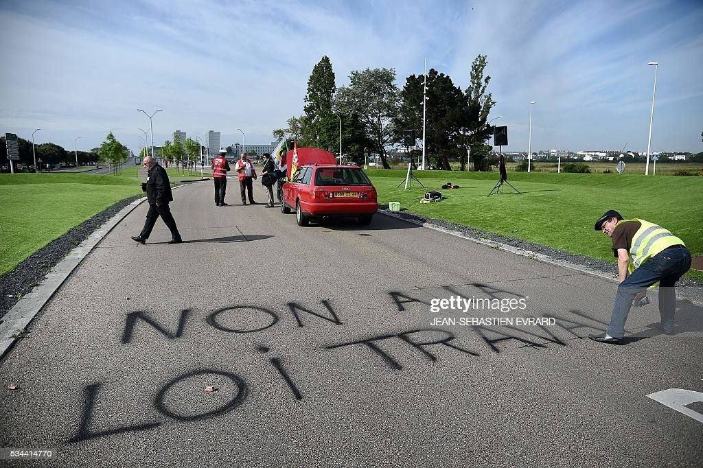 A protester sprays the words,'No to the labour law' as workers and union members gather on May 26, 2016 in Saint-Nazaire, western France, to protest against the government's planned labour law reforms. France's Socialist government has bypassed parliament and rammed through a labour reform bill that has sparked two months of massive street protests. / AFP / JEAN