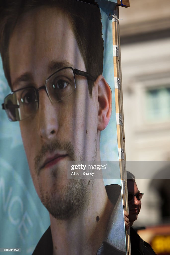 A protester stands behind a banner featuring the face of former National Security Agency employee Edward Snowden during the Stop Watching Us Rally...