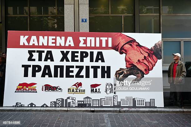 A protester stands by a huge banner reading 'No house in the hands of bankers' on November 19 outside of the finance ministery in Athens ahead of a...