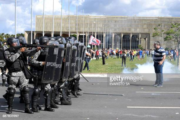 TOPSHOT A protester stands in front of a line of riot police during the protest 'Occupy Brasilia' against the labor and social security reforms and...