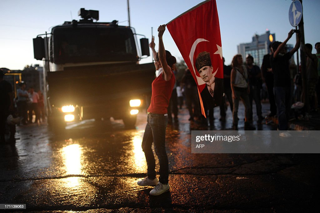 A protester stands in front of a police baricade with a Turkish flag featuring a portrait of modern Turkey's founder Mustafa Kemal Ataurk on it, in Taksim square in Istanbul on June 22, 2013 during a wave of new protests. Turkish police used water cannon today to disperse thousands of demonstrators who had gathered anew in Istanbul's Taksim Square, calling for the resignation of Prime Minister Recep Tayyip Erdogan.