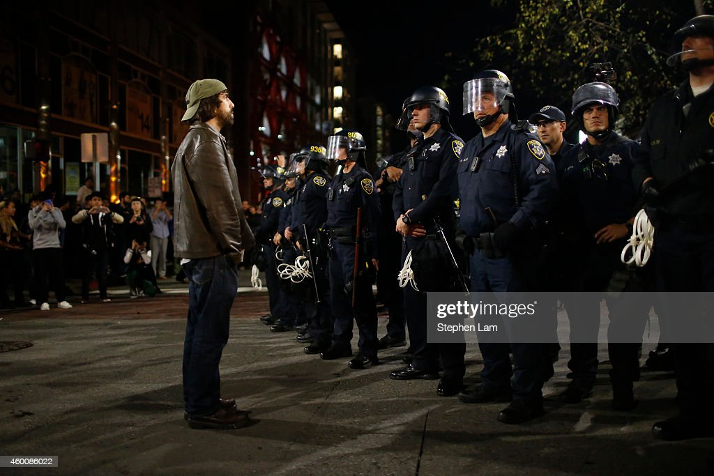 A protester stands in front of a police line during the fourth night of demonstrations over recent grand jury decisions in policeinvolved deaths on...