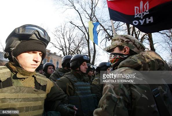 A protester stands in front of Ukrainian National Guard soldiers during a rally against trade with the occupied territories in Kiev on February 19...