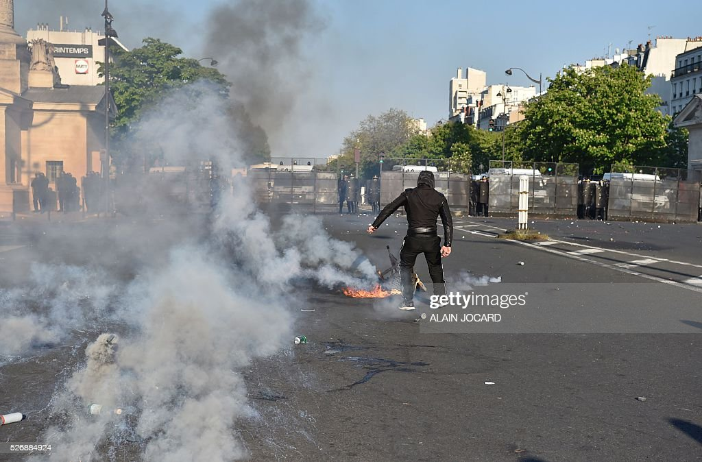 A protester stands near a fire during clashes with French anti riot police during the traditional May Day demonstration in Paris on May 1, 2016.