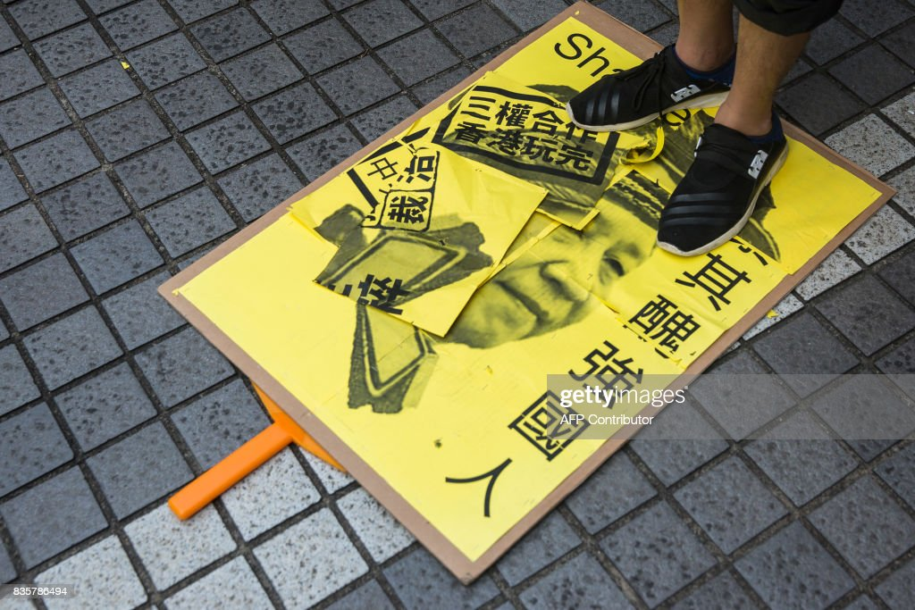 A protester stands on a placard of Chinese President Xi Jinping during a march in Hong Kong on August 20, 2017, to protest the jailing of Joshua Wong, Nathan Law and Alex Chow (not pictured), the leaders of Hong Kong's 'Umbrella Movement', after their sentencing at the High Court on August 17. Wong, Law and Chow were handed sentences of six to eight months by the Court of Appeal for their role in 2014's massive Umbrella Movement protests, which called for fully free leadership elections and were an unprecedented challenge to Beijing. /