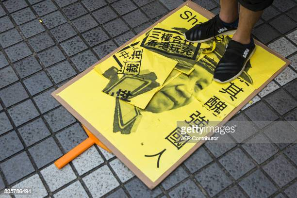 A protester stands on a placard of Chinese President Xi Jinping during a march in Hong Kong on August 20 to protest the jailing of Joshua Wong Nathan...