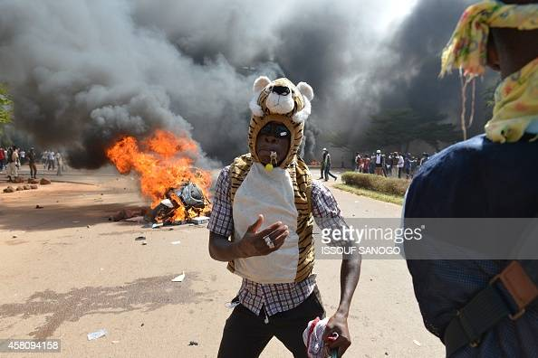 A protester stands outside the parliament in Ouagadougou on October 30 2014 as cars and documents burn outside Hundreds of angry demonstrators in...