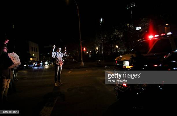 A protester stands with his arms raised against cop cars on the West Side Highway December 3 2014 in New York Protests began after a Grand Jury...
