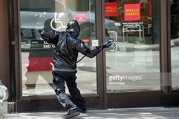 A protester swings a hammer towards the glass door of a Wells Fargo Co bank branch during an Occupy Seattle May Day rally and anticapitalist march in...