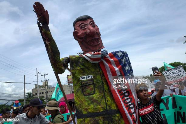 A protester takes a selfie as they push a caricature of President Rodrigo Duterte during a rally coinciding President Rodrigo Duterte's annual State...