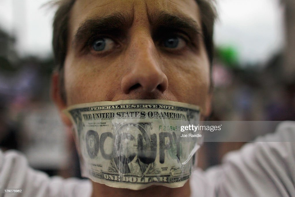 A protester tapes a one dollar bill over his mouth as he particpates in an Occupy Miami protest on October 15 2011 in Miami Florida Thousands of...