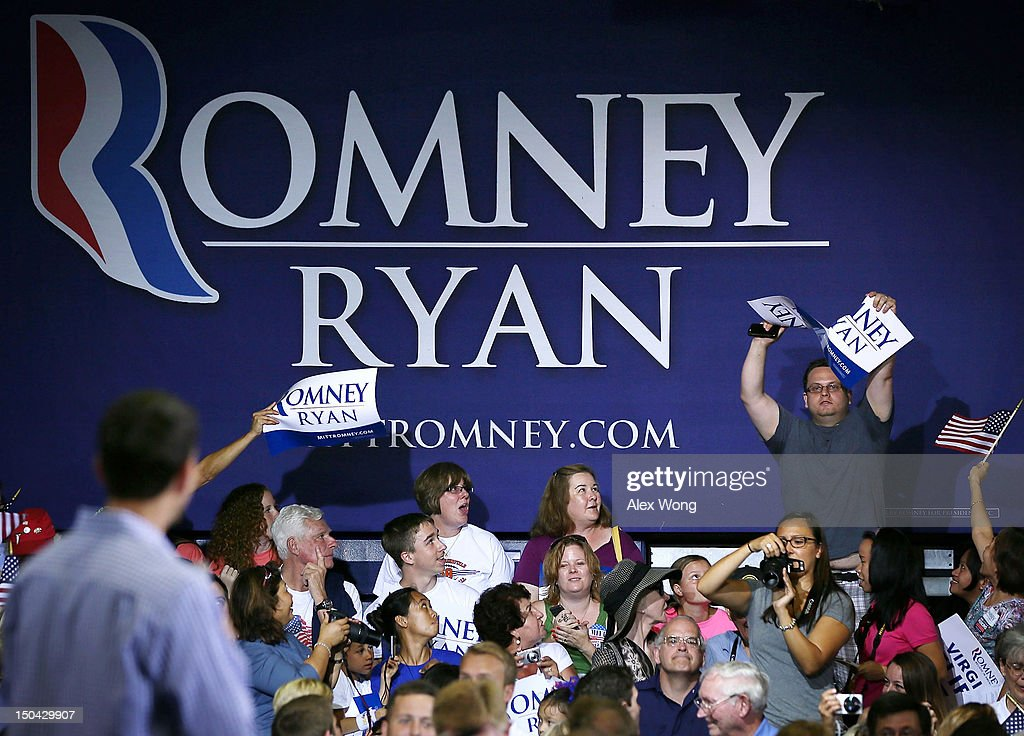 A protester tears a Romney-Ryan campaign sign in half as Republican U.S. Vice Presidential candidate Rep. Paul Ryan (R-WI) (L) watches during a campaign rally at West Springfield High School August 17, 2012 in Springfield, Virginia. Rep. Ryan continued to campaign After being named former Massachusetts Gov. Mitt Romney's choice for Vice President.