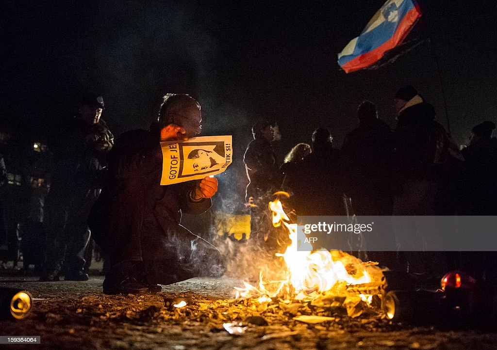 A protester throws a flyer with an image of Slovenian Prime Minister Janez Jansa and reading 'You are done' into a fire during a demonstration against political corruption and the Prime Minister in Ljubljana, on January 11, 2013. Several thousand people in Slovenia's capital today joined in one of the biggest anti-government rallies in recent months, demanding the resignation of Prime Minister Janez Jansa, who has been accused of corruption. State radio estimated over 10,000 people took part in the protest called by civil groups under the slogan 'For the government's resignation and the renewal of Slovenia.' Police put the figure closer to 8,000. AFP PHOTO / Jure Makovec