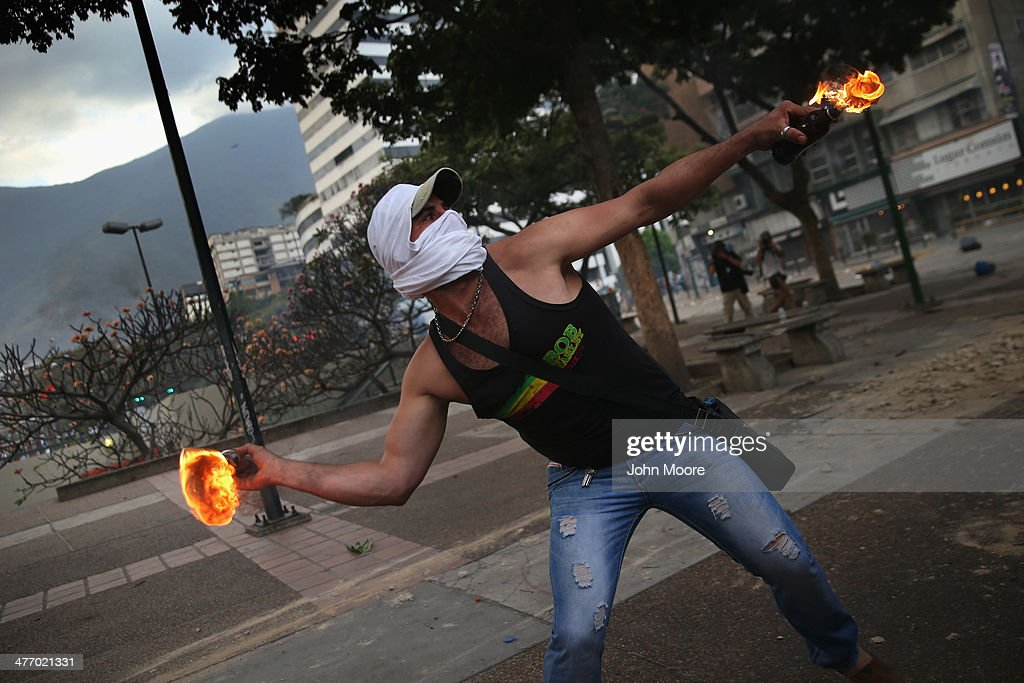 A protester throws a molotov cocktail at Venezuelan security forces during an anti-government demonstration on March 6, 2014 in Caracas, Venezuela. Three weeks of protests against the federal government have shaken the country as business in much of the nation has come to a standstill.