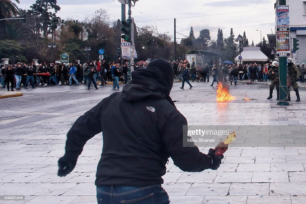 A protester throws a petrol bomb at riot policemen during a 24-hour nationwide general strike on February 4, 2016 in Athens, Greece. Clashes have broken out between Greek police and youths throwing fire bombs and stones, as tens of thousands of people march through central Athens to protest planned pension reforms.