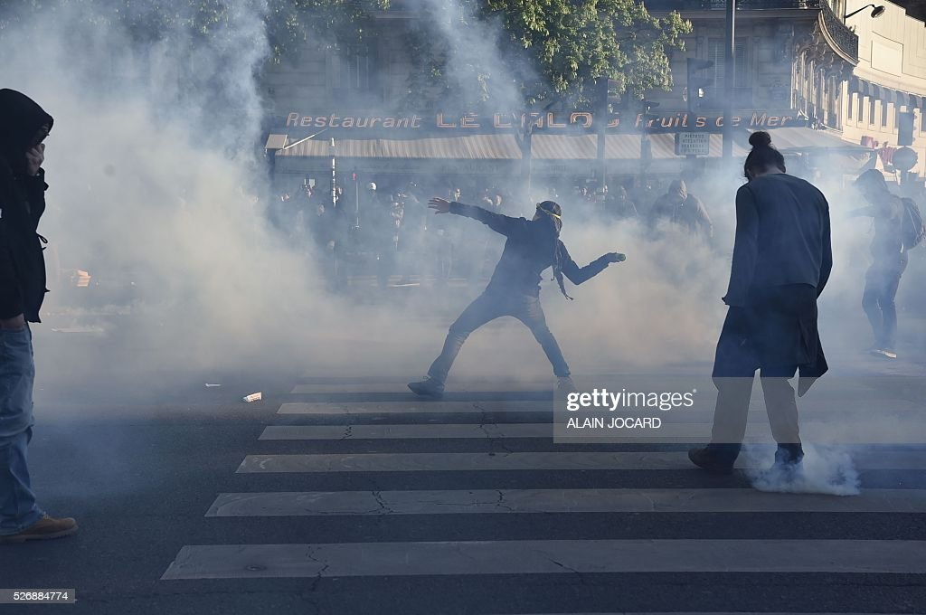 A protestor throws a projectile during clashes with French anti riot police during the traditional May Day demonstration in Paris on May 1, 2016.