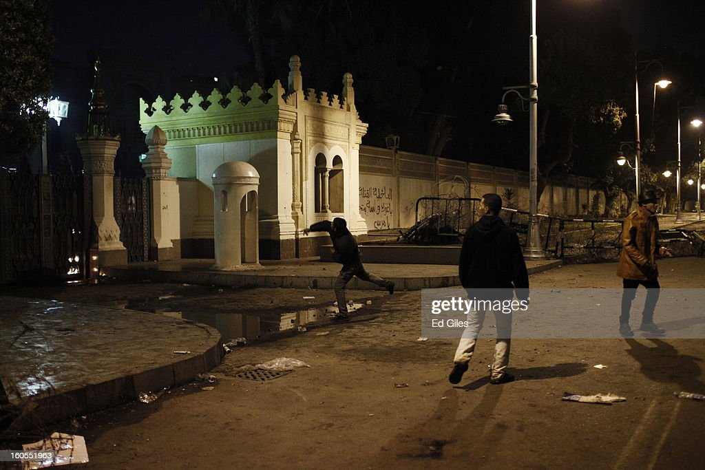 A protester throws a stone over the walls of Egypt's Presidential Palace during a demonstration following the commemoration march for a protester killed during clashes with Egyptian security forces the previous night, on February 2, 2013 in Cairo, Egypt. 23-year old protester Mohammed Hussein Korani was killed after sustaining gunshot wounds to the neck and chest during fighting with riot police outside Egypt's Presidential Palace in Cairo late on the night of February 1. Protests continued across Egypt nearly one week after the second anniversary of the Egyptian Revolution that overthrew former President Hosni Mubarak on January 25, 2011.(Photo by Ed Giles/Getty Images).