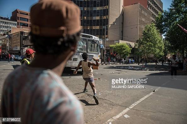 A protester throws a stone toward a bus during clashes with riot police following a protest over University tuition fees on October 10 2016 in...