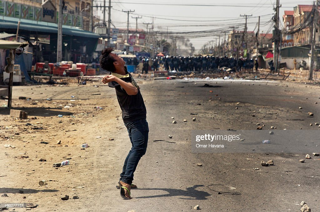A protester throws a stone towards a police line on during protests by garment workers on January 3, 2014 in Phnom Penh, Cambodia. Several people have been injured, and at least three people have reported dead after police broke up demonstrations on Veng Sreng Boulevard by garment workers demanding wage increases beyond the industry minimum wage set last week by the Ministry of Labour's Labour Committee.