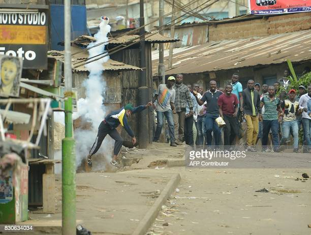 A protester throws a tear gas canister back during confrontations between Kenyan security forces and supporters of opposition coalition National...