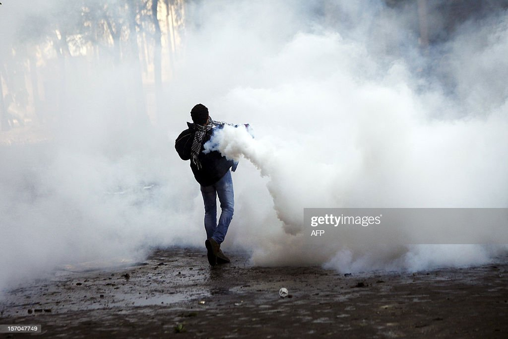 A protester throws back a tear gas canister during clashes with Egyptian riot Police on Tahrir Square on November 28, 2012 in Cairo. Police fired tear gas into Cairo's Tahrir Square, where several hundred protesters spent the night after a mass rally to denounce President Mohamed Morsi's assumption of expanded powers. AFP PHOTO / MAHMOUD KHALED