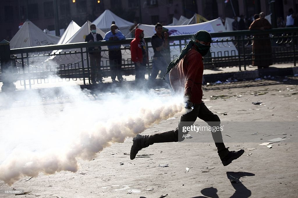 A protester throws back a tear gas canister during clashes with Egyptian riot Police on Tahrir Square on November 28, 2012 in Cairo. Police fired tear gas into Cairo's Tahrir Square, where several hundred protesters spent the night after a mass rally to denounce President Mohamed Morsi's assumption of expanded powers.