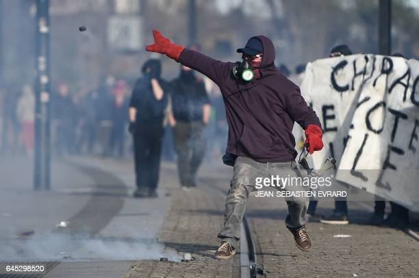 TOPSHOT A protester throws back a tear gas canister during clashes with riot police on the edge of a demonstration against the visit of French...