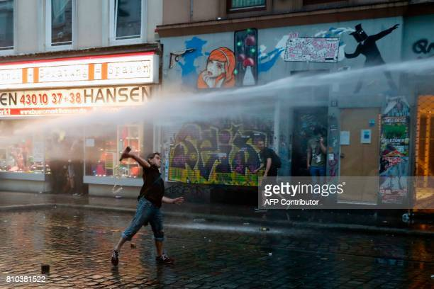 A protester throws bottles at riot police on July 7 2017 in Hamburg northern Germany where leaders of the world's top economies gather for a G20...