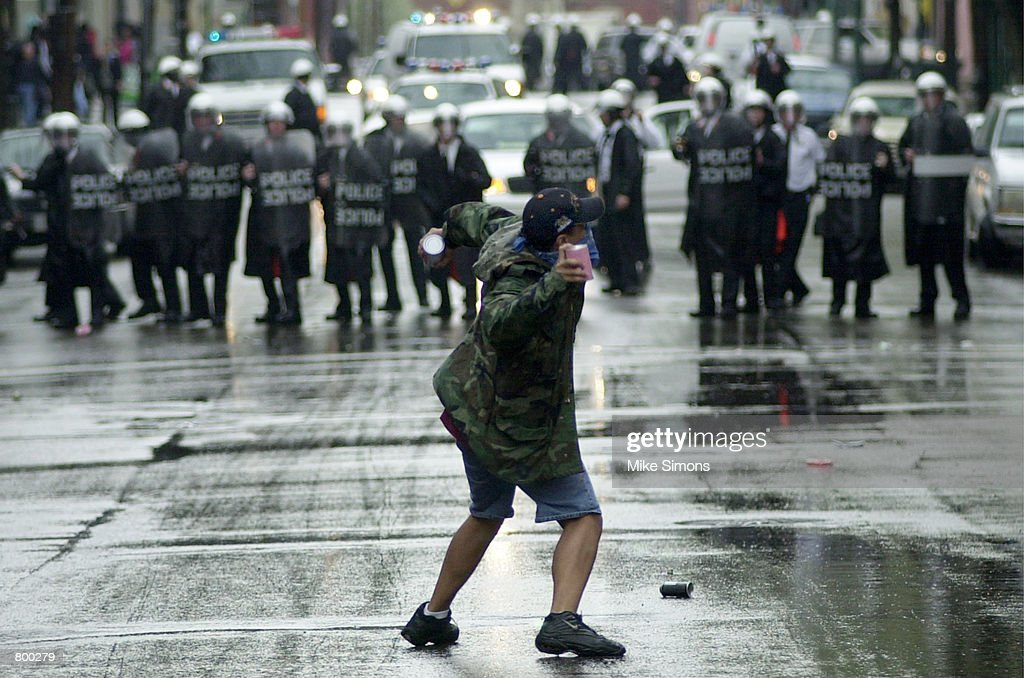 A protester throws debris April 10 2001 at Cincinnati Police Officers in riot gear in the Over The Rhine area in Downtown Cincinnati African American...