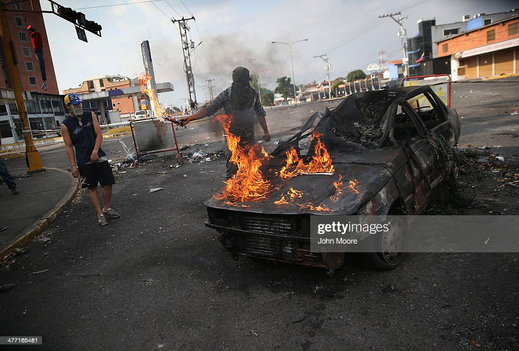 A protester throws gasoline on a burned out car during an anti-govenment protest on March 7, 2014 in San Cristobal, Venezuela. Protesters have set up barricades throughout San Cristobal, the capital of Venezuela's Tachira state, bordering Colombia. The state has been a focal point for anti-government protests for almost a month.