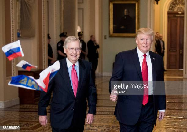 A protester throws Russian flags towards Senate Majority Leader Mitch McConnell RKy and President Donald Trump as they arrive for the Senate...