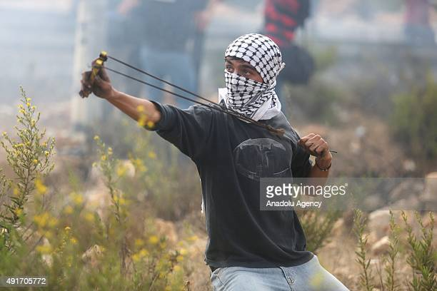 A protester throws stones to Israeli soldiers during a protest against preventing Palestinians from entering the AlAqsa Mosque compound on October 07...