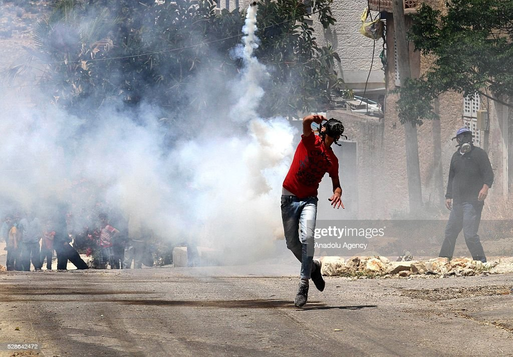 A protester throws tear gas canister to the security forces as a group of Palestinians protest the land expropriations by Israeli government at the village of Kafr Qaddum in the city of Nablus on the West Bank on May 6, 2016.