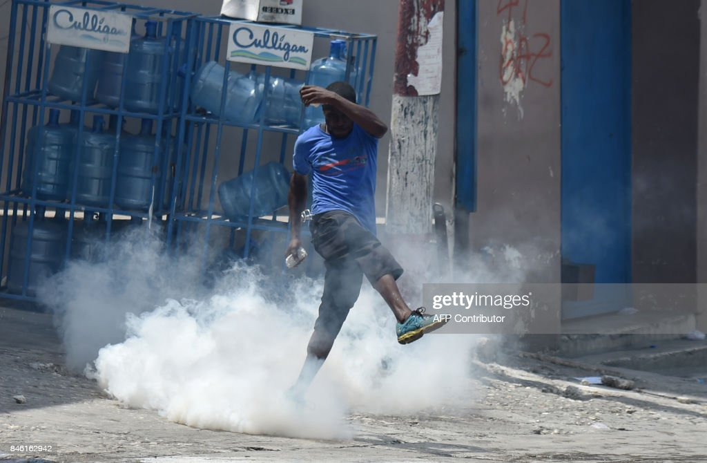 A protester tries to kick a tear gas canister fired by Haitian police during an anti-government protest in the centre of the Haitian capital Port-au-Prince, on September 12, 2017. Demonstrators took to the streets to protest against the government and the new budget for 2017-2018, throwing stones at the police, setting tires on fire and blocking some streets. /