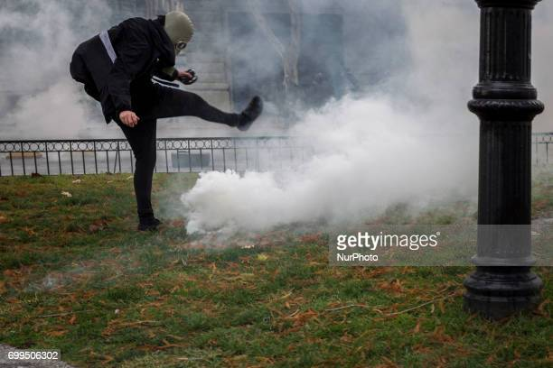 A protester tries to kick a teardrop canister launched by riot police Led by the Confederation of Chilean Students the march for universal education...