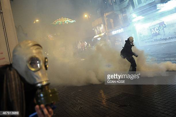 A protester tries to take a landing gas cannister during a protest against Turkish government's newly proposed restrictions on the use of internet on...