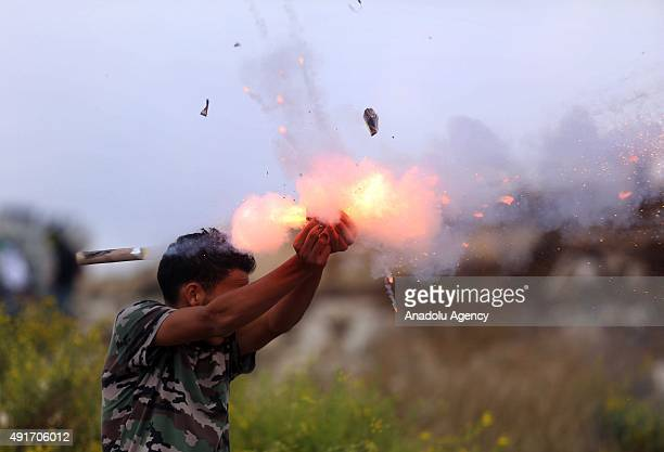 A protester uses a firework during clashes between Palestinian protesters and Israeli soldiers during a protest against preventing Palestinians from...