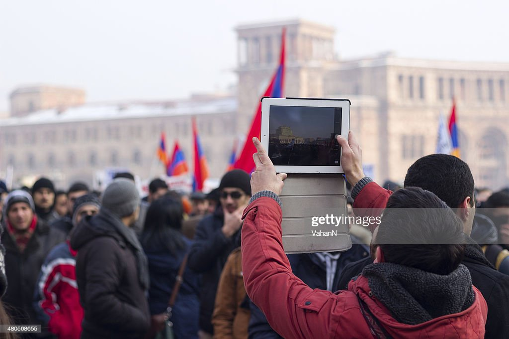 Protester uses a tablet to photograph protest demonstration : Stock Photo