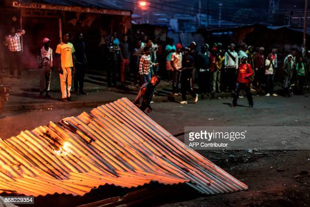 A protester uses a tin roof to build a burning barricade in the Mathare slums in Nairobi on October 30 during demonstrations following the...