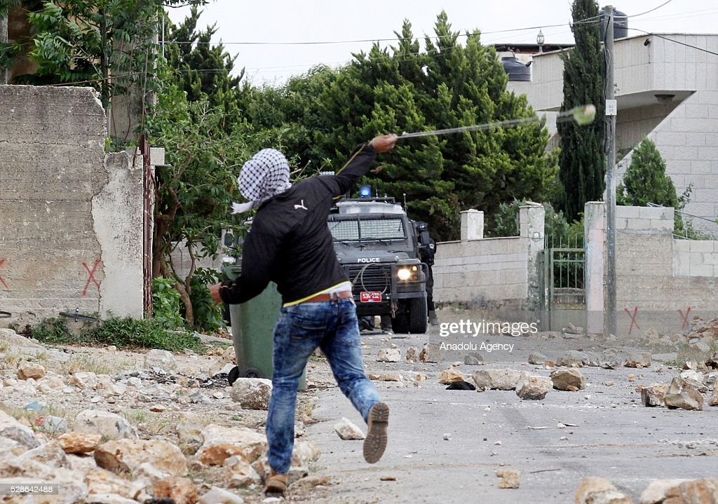 A protester uses slingshot as a group of Palestinians protest the land expropriations by Israeli government at the village of Kafr Qaddum in the city of Nablus on the West Bank on May 6, 2016.