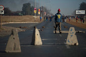 A protester walks among concrete blockading an intersaction during a service delivery protest on July 22 2016 ahead of August 3rd municipal elections...